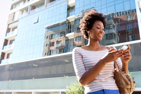 携帯電話が付いている都市の若い女性の肖像画