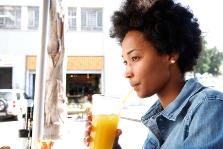 a straw: Portrait of fashionable young african woman sipping orange juice