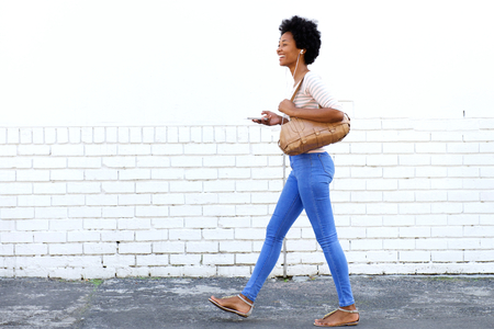Full length portrait of woman walking on sidewalk with headphones and purse