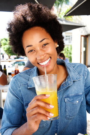 Close up portrait of smiling woman drinking orange juice at cafe