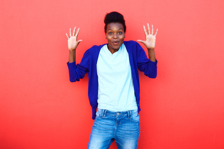 woman looking: Portrait of surprised young woman standing with her hands raised against red background Stock Photo