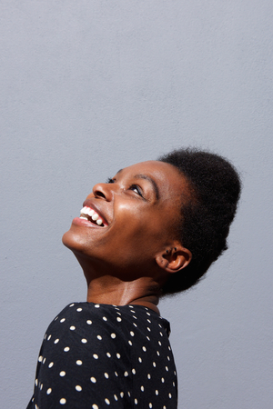confident woman: Close up side portrait of cheerful young african woman smiling against gray background