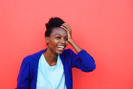 excited woman: Portrait of excited young african woman laughing with her hand on head against red background