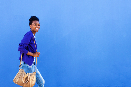 Portrait of smiling young african woman walking against blue wall