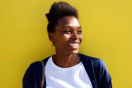 happy african: Close up portrait of beautiful young african woman looking away and smiling against yellow background