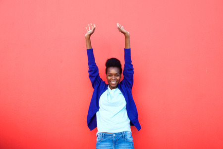 excited woman: Portrait of excited young african woman standing with her arms raised against red background