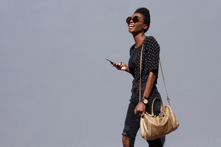 Portrait of stylish young african american woman walking with bag and mobile phone
