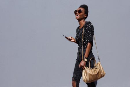 Portret van stijlvolle jonge Afro-Amerikaanse vrouw lopen met tas en mobiele telefoon