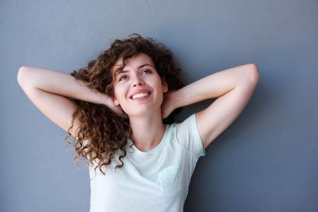 hands on head: Portrait of smiling teen girl standing with hands behind head