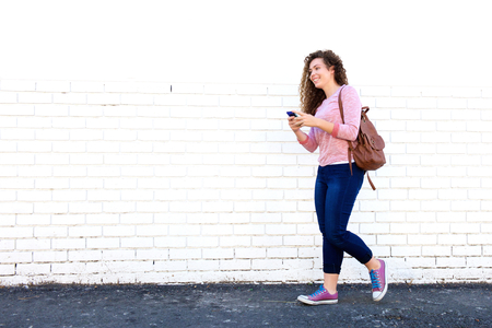 Portrait of smiling teen girl walking with cellphone and backpack 스톡 콘텐츠