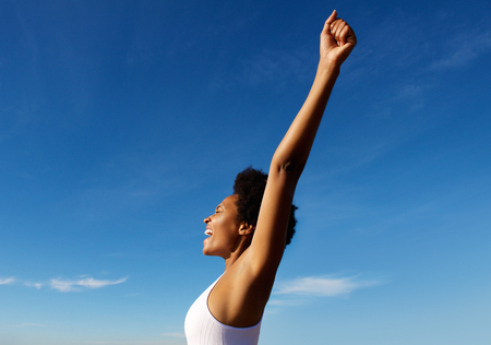 hands raised sky: Side view portrait of excited fitness woman standing outdoors against blue sky with her hands raised Foto de archivo