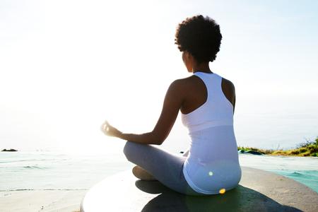 Achter portret van de jonge Afro-Amerikaanse vrouw, zittend op het strand in yoga stelt