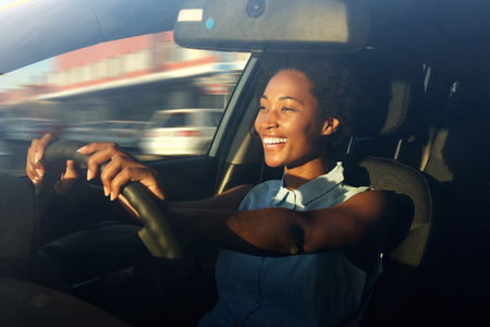 Portrait of smiling young african american woman driving a car Archivio Fotografico