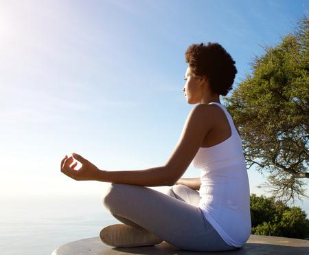 Zij portret van mooie jonge vrouw zit in yoga pose op het strand Stockfoto