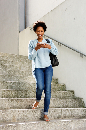 Full length portrait of smiling young african woman walking down the stairs and reading text message on her mobile phone 版權商用圖片