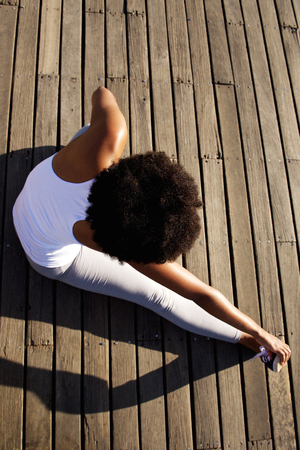 topdown: Top view portrait of young woman sitting on wooden boardwalk and doing stretching exercise at beach Stock Photo