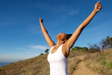 Portrait of overjoyed african woman standing outdoors with her arms wide open and looking towards sky
