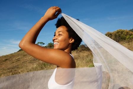 Hermosa mujer joven sosteniendo la tela blanca en el viento en un día de verano Foto de archivo