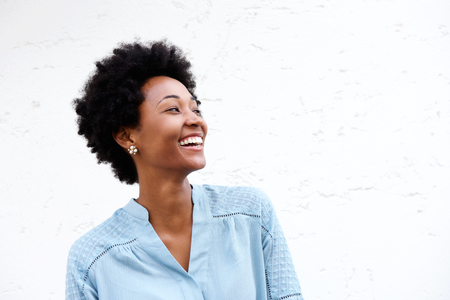 Close up portrait of beautiful young black woman looking away and smiling against white background