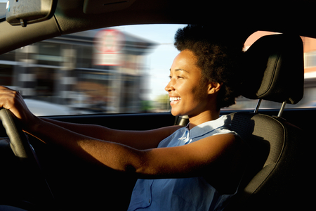 Side portrait of happy young african woman driver driving a car Stockfoto