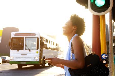 Cerca retrato lateral de la mujer afroamericana sonriente con el teléfono celular en la calle de la ciudad Foto de archivo