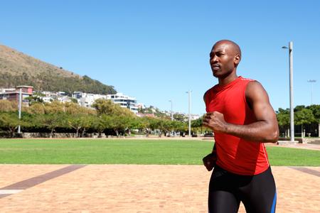 sportsman: Retrato de joven deportista africano corriendo afuera en el parque