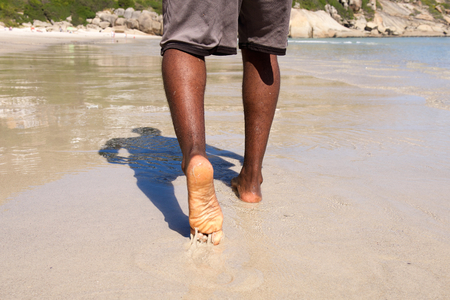 barefoot man: Close up rear view of man walking with bare feet on the beach