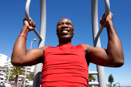 pull up: Portrait of african man doing pull up exercise workout outdoors