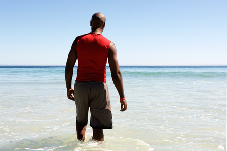 black male: Rear view portrait of african man walking in to the sea water