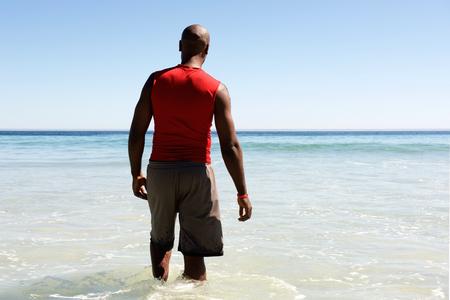 hombres negros: Vista trasera retrato de hombre africano que camina en el agua de mar