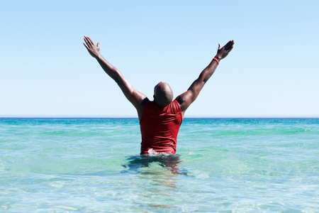 Vista posteriore ritratto di uomo africano in piedi in mare con le mani alzate e guardando il cielo