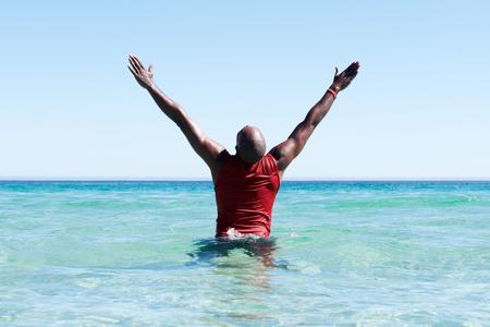 Vista trasera retrato del hombre africano de pie en el mar con las manos levantadas hacia arriba y mira el cielo Foto de archivo