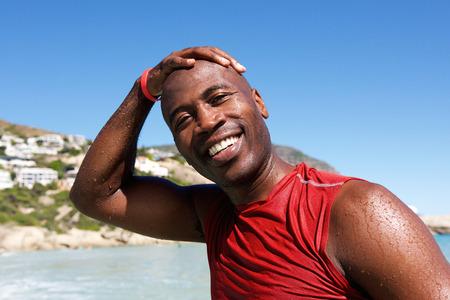 Close-up portret van vrolijke jonge afro Afrikaanse man op het strand na zwemmen Stockfoto