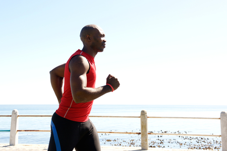 black male: Side portrait of fit exercising african man jogging outdoors on seaside promenade on a sunny day