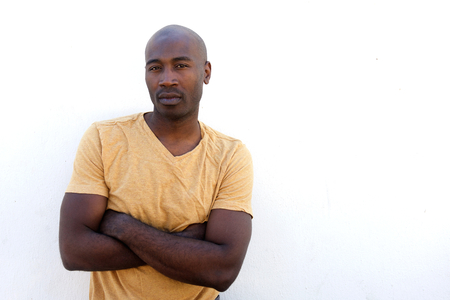 Portrait of confident young black man with arms crossed standing against white wall Stock Photo