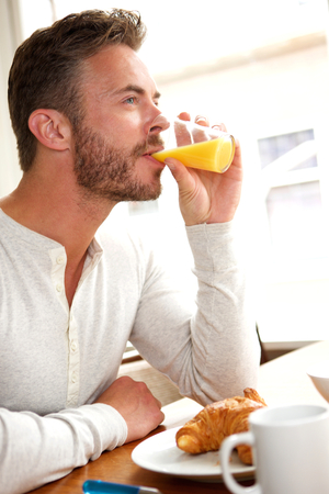 tomando jugo: Portrait of handsome middle age man drinking juice with breakfast