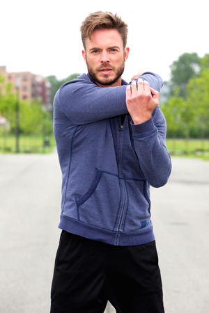 male athlete: Portrait of male athlete doing stretch outside