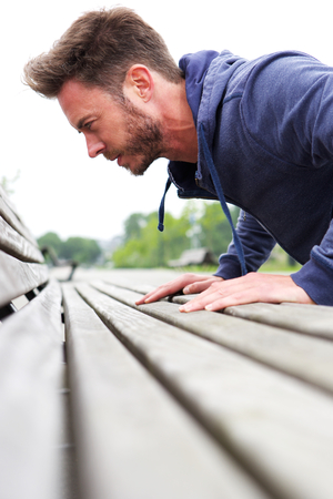 pushup: Close up portrait of attractive male doing pushup on bench Stock Photo