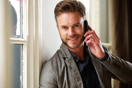 male fashion model: Close up portrait of handsome professional man standing with phone