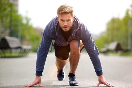Portrait of healthy runner in starting position outside