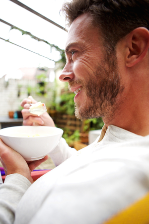 mid adult men: Close up side profile portrait of cheerful older man eating healthy breakfast