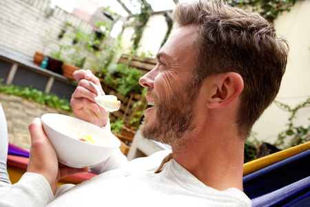 profil: Close up side profile portrait of happy man eating fruit salad outside