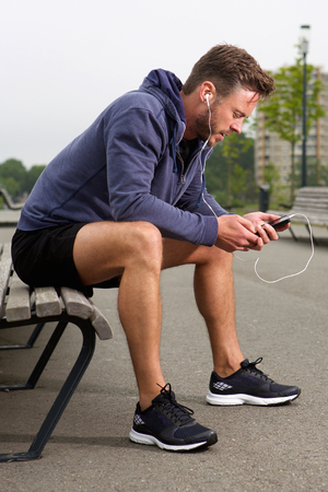 male body: Full body portrait of male athlete listening to music Stock Photo
