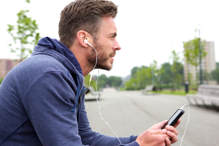 active listening: Side profile portrait of middle age active male sitting and listening to music Stock Photo