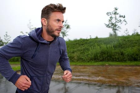 Seitenporträt des entschlossenen älteren Läufers draußen im Regen Standard-Bild - 61162198