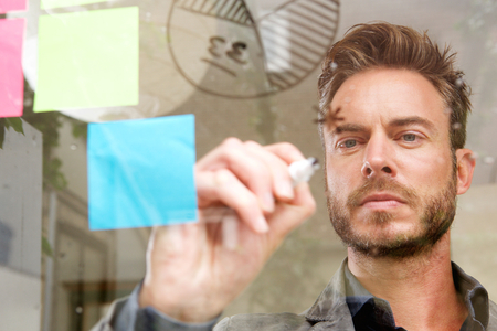 writing on glass: Portrait of handsome man writing on transparent idea board thinking