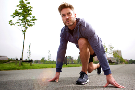 starting position: Portrait of male runner training in starting position Stock Photo