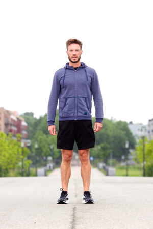 male athlete: Full length portrait of attractive male athlete standing in middle of street Stock Photo