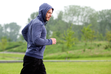 man profile: Side profile portrait of athletic middle age man running park Stock Photo