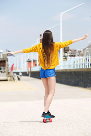 style woman: Full length portrait from behind of woman balancing on skateboard outside Stock Photo